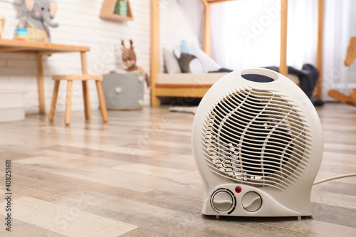 Obraz Modern electric fan heater on floor at home. Space for text - fototapety do salonu