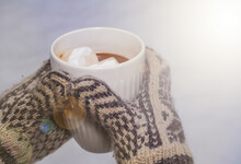 Hands In Knitted Mittens Holding A Cup Of Hot Chocolate With Marshmallows In A Snowy Environment.