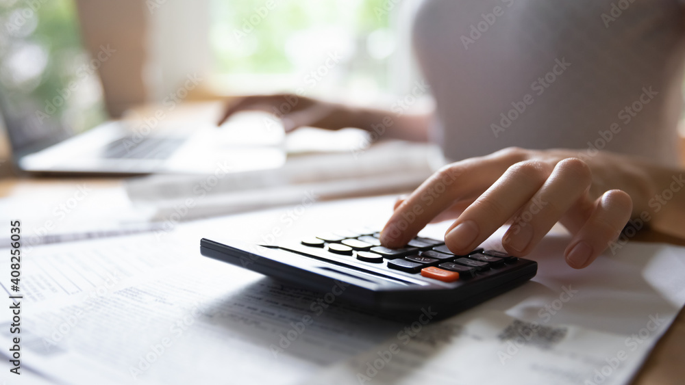Fototapeta Calculating expenses. Close up of young female hand counting on portable electronic calculator estimating money income. Housewife planning family budget or managing payments for utility services.