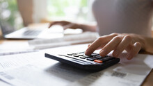 Calculating Expenses. Close Up Of Young Female Hand Counting On Portable Electronic Calculator Estimating Money Income. Housewife Planning Family Budget Or Managing Payments For Utility Services.