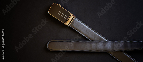 Canvas-taulu A men's black leather belt with an automatic golden buckle lies against a dark background