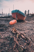 A Wooden Boat And Anchor Chain At Low Tide