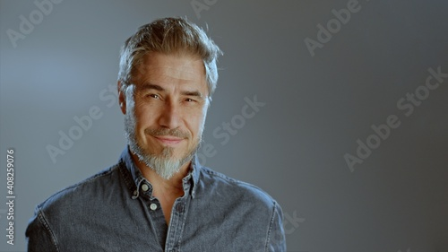 Obraz Portrait of happy older white man, beard gray hair, smiling. Copy space for text gray background, - fototapety do salonu
