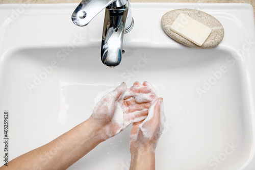 Billede på lærred A Hands with soap are washed under the tap with water