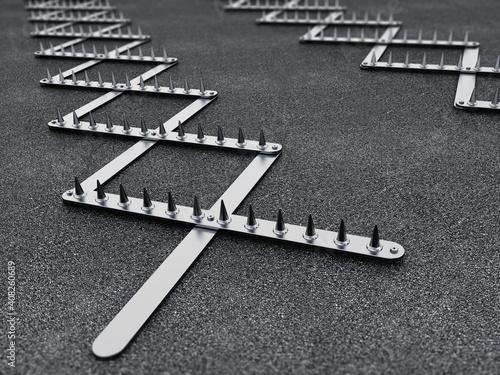 Road spike or tire trap on asphalt background. 3D illustration © Destina