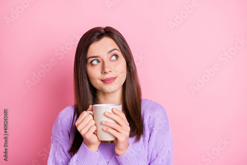 Portrait of optimistic girl hold cup look empty space wear lilac sweater isolated on pink color background © deagreez