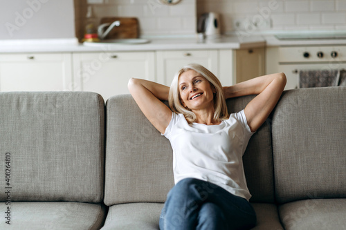 Fototapeta Happy mature caucasian woman is relaxing on the couch in living room at home. Middle aged woman enjoying weekend or leisure from homework sitting on sofa, looks away and smiling obraz