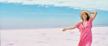 Panoramic Image Freedom Woman In Pink Dress And Hat With Open Arms On Blue Sky White Salt Beach Landscape. Feeling Happiness Enjoying Her Travel Vacation. Design Banner With Copy Space
