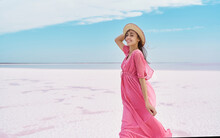 Happy Carefree Elegant Woman In Blowing Pink Dress Enjoys Her Vacation While Walking Along White Salty Beach On Salt Lake With Paradise View