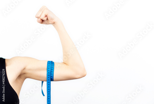 Vászonkép Young woman biceps in fitness wear isolated on white background.