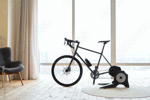 Foto Stationery exercise bike in apartment with wooden floor