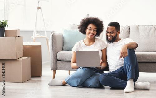 Obraz Black Couple Using Laptop Sitting Among Moving Boxes In House - fototapety do salonu