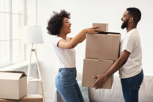 Happy African Couple Packing Moving Boxes Together Standing Indoors