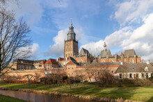 Sunlit Soft Picturesque View Of Winter Landscape And Rising Church Tower Above The Cityscape Of Medieval Hanseatic City Zutphen In The Netherlands Against A Blue Sky With Fluffy Clouds
