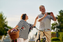 Happy Aged Tourists With Bikes And Photo Camera. Loving Senior Couple Outdoors.