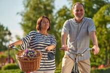 Elder Man And Woman Outoodrs In The Park. Aged Caucasian Couple With Bikes And Flowers.