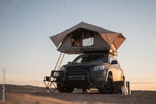 Photo Rooftop tent for camping on the roof rack of an off-road SUV car in a desert