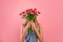 Flowers For Special Occasion. Anonymous Young Lady Holding Bouquet Of Tulips In Front Of Her Face Over Pink Background