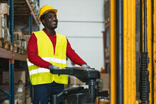 Black Man Working In Warehouse With Forklift Loading Delivery Boxes - Logistic And Industry Concept