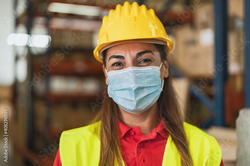 Obraz Happy Latin woman working in warehouse while wearing face mask during corona virus pandemic - Logistic and industry concept - fototapety do salonu