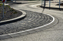 Roundabout Of Paving Of Gray Granite Cubes In A Rolled Sill Closer To The Center. Beveled Concrete Curbs, A Transport Hub, With Flowers And Grasses In The Middle Of The Circle. Perennial Flowerbed