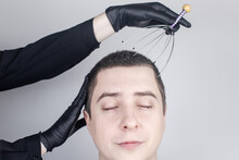 A Man Is Given A Head Massage With A Capillary Massager In The Salon. The Client's Face Shows Relaxation And Joy. The Concept Of Anti-stress Massage And The Provision Of Services By A Masseur.