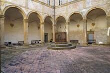 Chiostro Di Un Antico Castello , Con Archi In Veduta Simmetrica Con Al Centro Un Pozzo Con Decorazione In Ferro