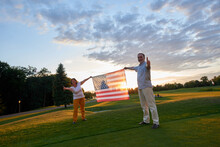 Couple Holding Us Flag And Showing Thumb Up. Patriotic Man And Woman On The Green Field.
