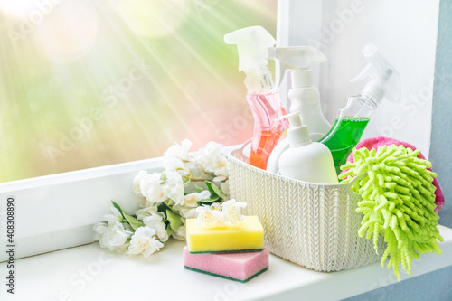 Obraz Spring cleaning concept - cleaning supplies and flowers on blur background, copy space - fototapety do salonu