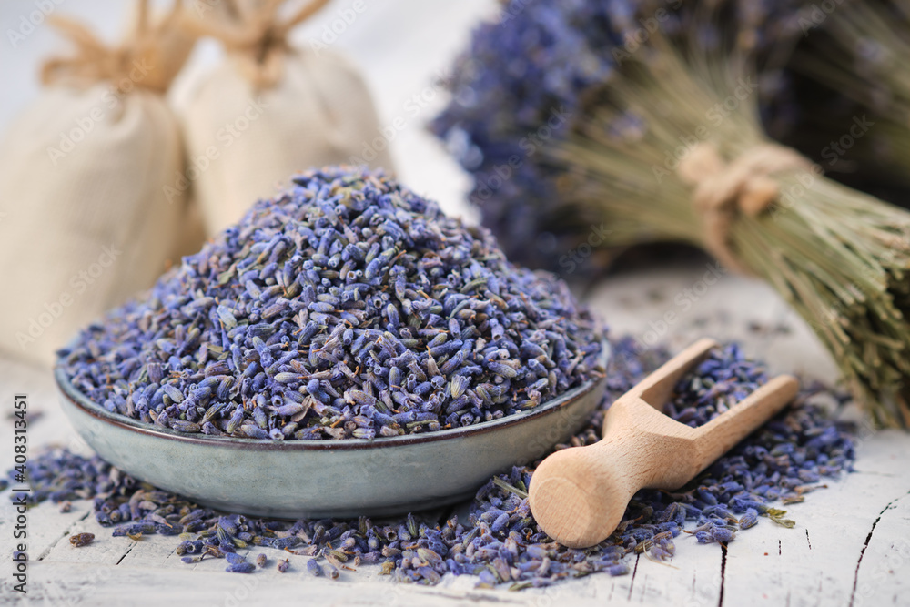 Fototapeta Blue plate of dried lavender. Wooden scoop of dry lavender flowers. Lavender bouquet and sachets on background.