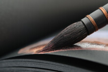 Close Up Of A Artistic Paintbrush For Watercolor Painting. Painting With A Brush In A Sketchbook On Black Paper Sheet.