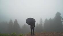 A Man Holding An Umbrella In Kumbet Plateau. Foggy Weather. 4K Footage In Turkey