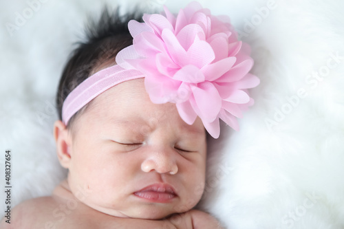 Obraz A beautiful newborn girl wearing a pink headband and sleeping on a white soft blanket, Infant, babyhood concept and copy space - Image - fototapety do salonu