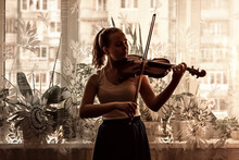 Silhouette Of A Young Girl, A Musician. Playing The Violin In The Background Of The Window