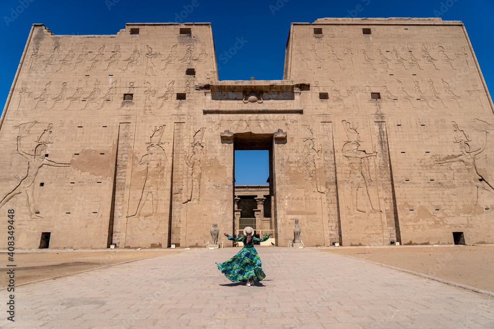 Fototapeta Edfu / Egypt - 02 09 2020: The Temple of Horus at Edfu, A large Ancient Egyptian temple. Women in green dress walking to the gate.
