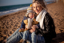 Happy Family, Mother With Son Walking Wirh Fun In The Sea Shore On Windy Day. People Dressed Warm Clothes.