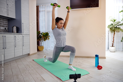 Fotografia Young sporty woman holding dumbbells and rainsing her arms up while doing lunges