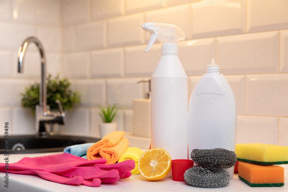 Fototapeta Cleaning products, citron and sponges on kitchen countertop with in background blurred sink.
