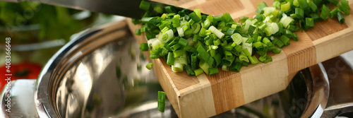 Obraz Close up of cook putting onions in a pan in the kitchen at home while making soup. Cooking recipes concept - fototapety do salonu