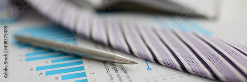 Obraz Close up of metal pen lying on documents on a desktop with notebook on the background. Reporting and accounting concept - fototapety do salonu