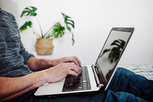 Man Working On Laptop While Sitting At Home