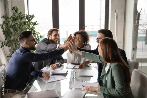 Obraz Excited diverse business team giving high five at briefing, sitting at table in boardroom, motivated for shared success, overjoyed colleagues joining hands, engaged in team building activity - fototapety do salonu