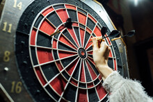 Woman's Hand Collecting Darts From Board