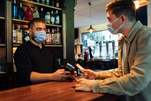 Male Customer Paying With Credit Card To Waiter In Bar During Pandemic