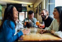 Smiling Friends Having Drinks At Restaurant
