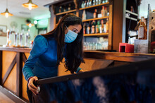 Mid Adult Woman Wearing Protective Face Mask Playing Pinball In Bar During Pandemic