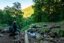 Female Hiker Sitting On Rock While Exploring Swabian Alb Mountain, Germany