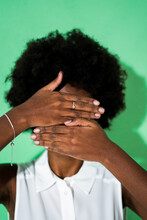 Young Woman Hiding Face With Hand While Standing Against Green Background
