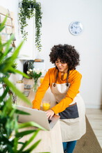 Young Woman With Orange Juice Using Laptop While Standing At Home