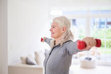 Smiling Senior Woman Exercising With Dumbbells At Home